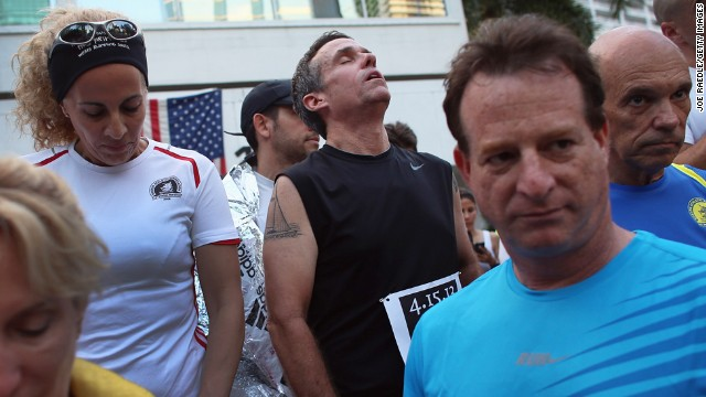 Five-time Boston Marathon runner Jose Sotolongo, center, reacts during a moment of silence at the Baptist Health South Florida Brickell Run Club event in Miami on April 16.