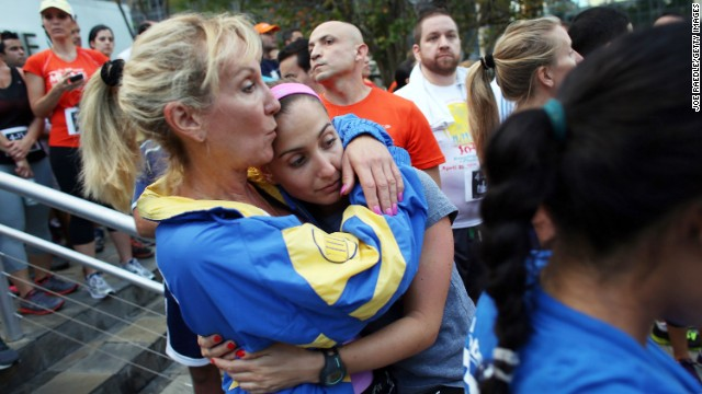 Runners Judy Adler, left, and her daughter, Rachel Schapiro, embrace during a moment of silence at the Baptist Health South Florida Brickell Run Club event organized on April 16 in Miami in honor of victims of the Boston Marathon bombings.