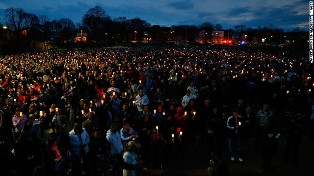 A crowd holding candles gathers during a vigil on April 16 at Garvey Park in Boston for 8-year-old Martin Richard of Dorchester, who was killed in the marathon bombing.