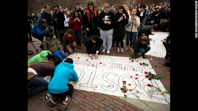 Attendees of the vigil sign a large poster in honor of the victims of the bombing on April 16.