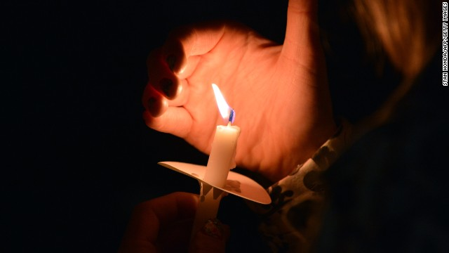 A woman uses her hand to keep wind from her candle as she stands with others around the pond in the Boston Public Gardens after a candlelight interfaith service at Arlington Street Church on April 16.