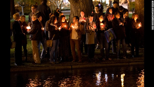 Mourners gather on the edge of the pond in the Boston Public Gardens for a candlelight vigil on April 16.
