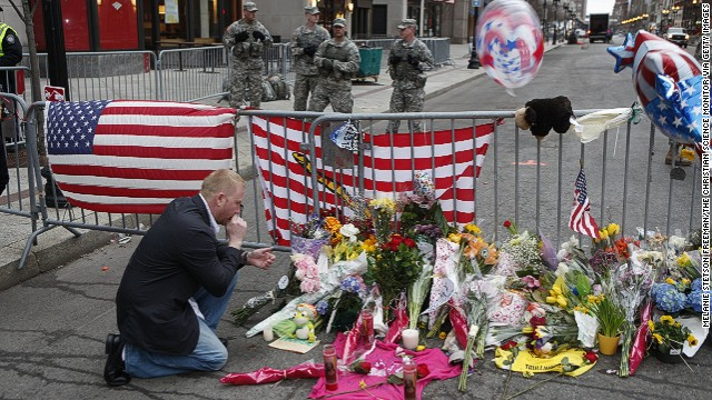Mike Vitale, who lives in the Boston area, prays beside a makeshift memorial at a roadblock at the end of Boylston Street.
