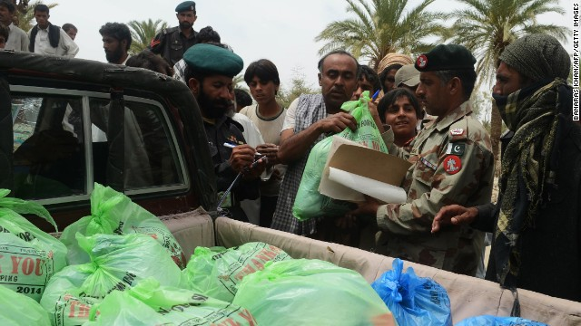 A Pakistani military official distributes relief supplies Wednesday in Mashkell.