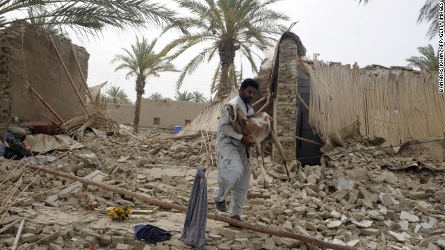 An earthquake survivor carries a goat through the rubble in