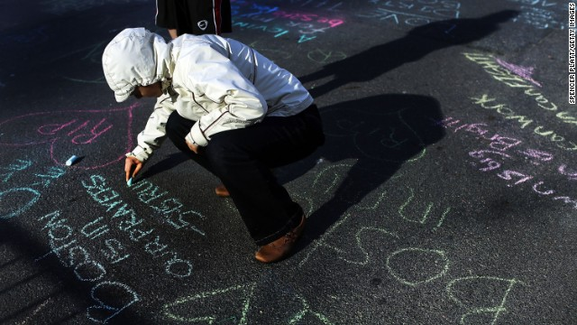 Danielle Cerroni writes a chalk message on the street on April 17 at the scene of the explosions near the finish line of the Boston Marathon.