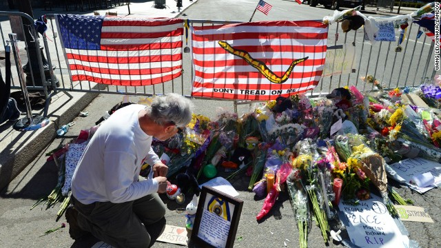 A man places a message for the victims of the Boston bombings at a memorial site in Boston on April 17.