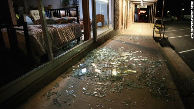 Glass from blown-out windows lies shattered on the sidewalk and street after the blast on April 18.