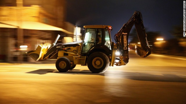 Earth-moving equipment rolls through the downtown area in the middle of the night on April 18.
