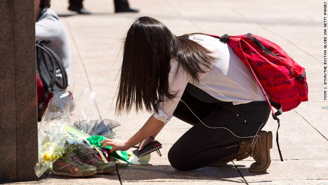 "Joy Liu, 23, puts a green hat with a shamrock and a note with the words ""From Boston and Beijing with love. RIP"" at the memorial for Lu."