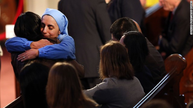 A nun hugs a woman at the interfaith prayer service.