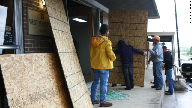 Workers board up a furniture shop with shattered windows on Thursday.