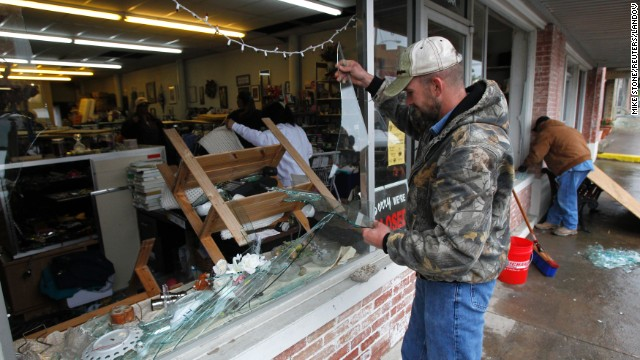 Brandon Smith removes broken glass from the West Thrift Shop on Thursday.