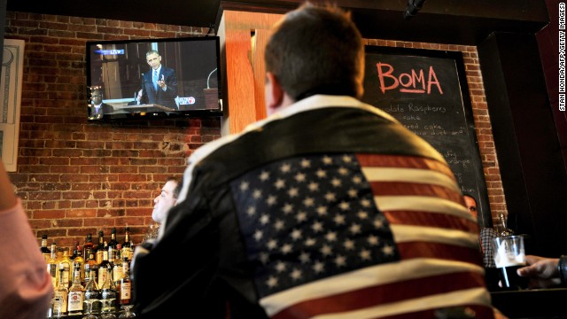 A man at the BoMA restaurant across the street from the Cathedral of the Holy Cross in Boston watches President Obama speak on television at the cathedral honoring the victims of the Boston Marathon bombings on April 18.