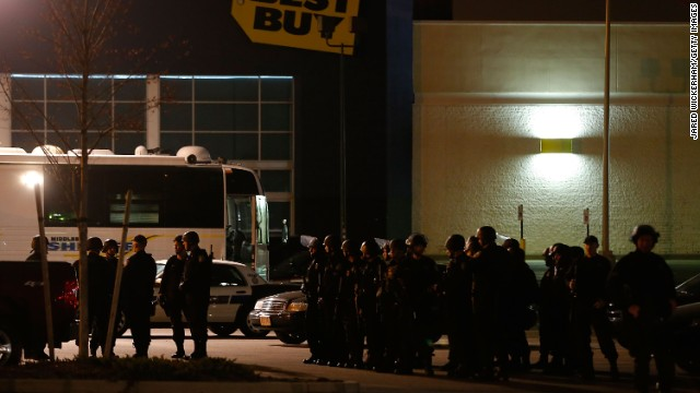Boston Police gather in the parking lot in front of a Best Buy store near the Watertown Mall on Friday.