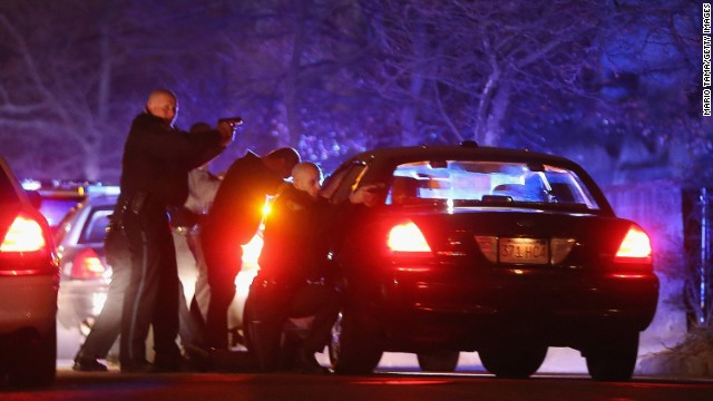 Police with guns drawn search for a suspect on Friday in Watertown, Massachusetts.