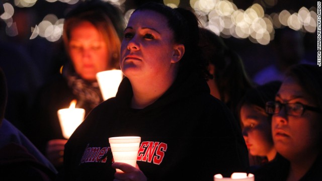 People hold candles as they listen to a speaker during a vigil in Somerville, Massachusetts, on April 18.