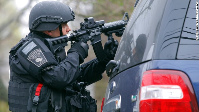 A SWAT team member trains a gun on an apartment building during the search for a suspect in the Boston Marathon bombings.