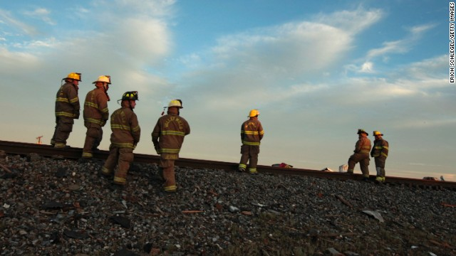 Fire personnel check out the railroad tracks near the fertilizer plant on April 18.