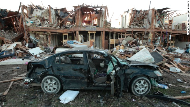 The remains of a car sit in front of an apartment complex destroyed after the fertilizer plant blast.