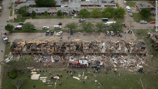 Search and rescue workers comb through what remains of a 50-unit apartment building, in foreground, and a nursing home on April 18.