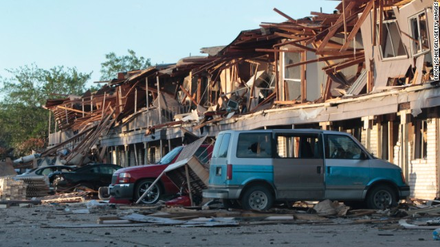 The remains of an apartment complex lie on cars on April 18.