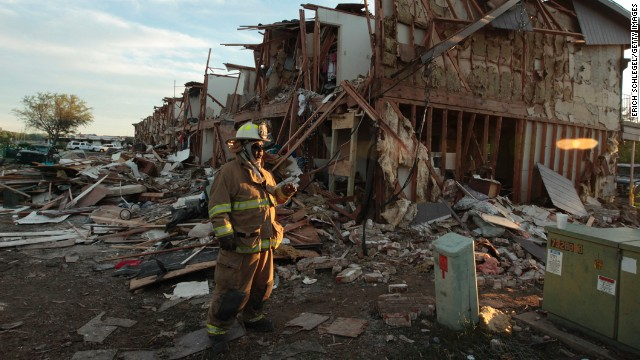 A Valley Mills Fire Department firefighter walks through the remains of an apartment complex next to the fertilizer plant.