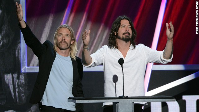 Taylor Hawkins, left, and Dave Grohl of the Foo Fighters help induct Rush into the Rock and Roll Hall of Fame.