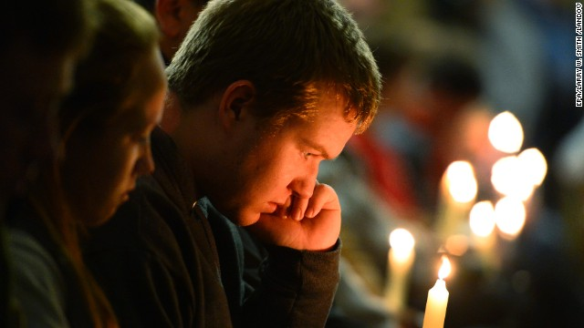 A young man holds a candle during the vigil.