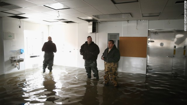 Workers inspect flood damage inside a vacant commercial building on April 19 in Des Plaines, Illinois.