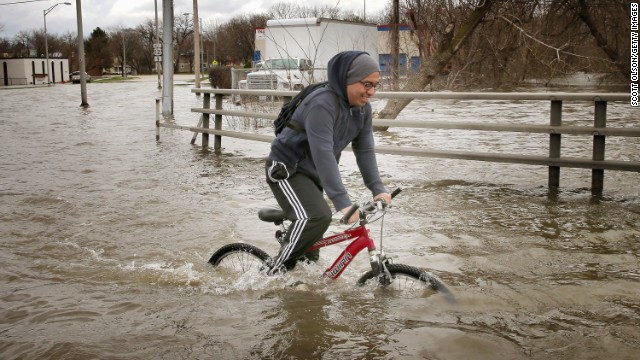 Hector Duran uses his bike to get through floodwater on Friday, April 19, in Des Plaines, Illinois. The suburban Chicago town is battling rising floodwater from the Des Plaines River.