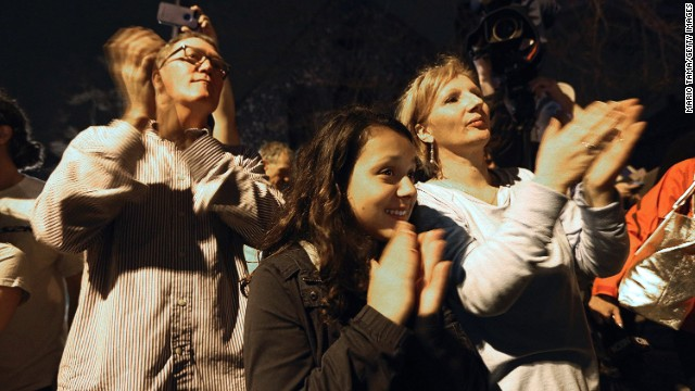 Onlookers applaud first responders departing the scene at the end of the manhunt on April 19.