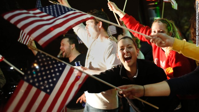 People wave U.S. flags as police drive down the street in Watertown on Friday around 9 p.m. after it was announced that Dzhokhar Tsarnaev had been captured.