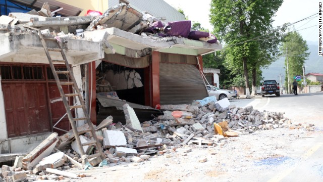 Rubble covers roadside houses in Longmen on Saturday.