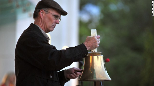 A man rings a bell at the vigil in Huntsville on April 19.