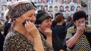 Russians cry inside the Beslan school gym remembering when at least 300 kids and parents were killed by Chechen rebels in 2004. \n