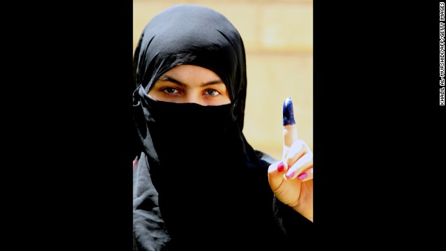 An Iraqi woman shows her ink-stained finger, indicating she cast a ballot at a polling station on Saturday.