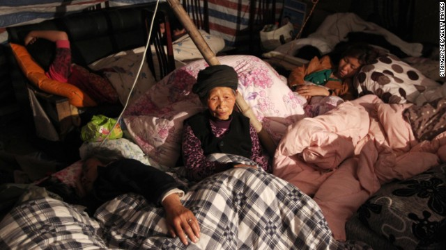 A family rests in a makeshift shelter in Lushan on Sunday.