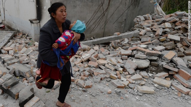 A mother carries her baby through rubble in Lushan County in Sichuan, China, on Sunday, April 21. A 7.0-magnitude earthquake hit China's southwest Sichuan Province on April 20. At least 180 people have died and another 24 are missing.