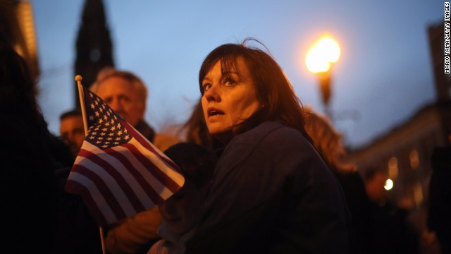 A woman holds an American flag at a makeshift memorial on April 20, near the scene of the Boston Marathon explosions.