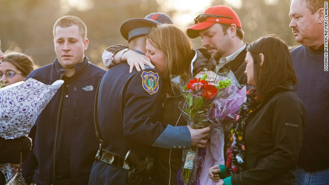 Nicole Collier Lynch, center, sister of slain MIT police officer Sean Collier, hugs a Wellesley police officer during a vigil at the Town Common in Wilmington, Massachusetts, on Saturday, April 20. Collier, 26, was shot multiple times in his car on Thursday night as Boston Marathon bombing suspects Dzhokhar Tsarnaev and his brother Tamerlan tried to evade capture.