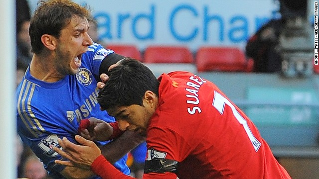 Liverpool striker Luis Suarez (R) clashes with Branislav Ivanovic after appearing to bite the Chelsea player in the second half of Sunday's 2-2 draw.