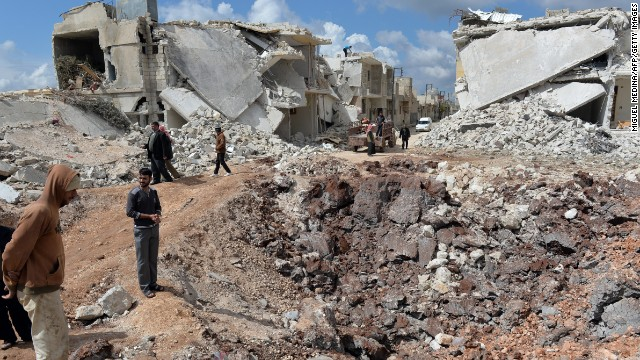 People walk past destroyed houses in the northern Syrian town of Azaz on Sunday, April 21. 