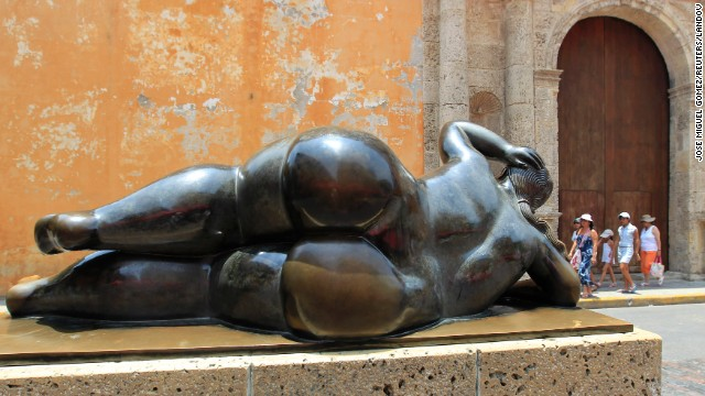 Tourists walk past a sculpture by Fernando Botero in Cartagena's old city in April 2012.