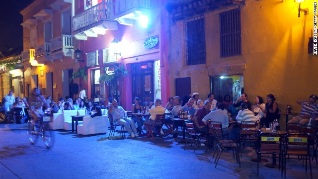 People sit outside restaurants and bars situated on the corner of a small square inside the city walls in January 2012 in Cartagena.