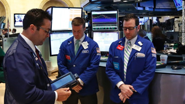 Traders on the floor at the New York Stock Exchange join the moment of silence on April 22.
