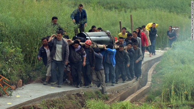 Villagers carry the coffin of a man killed in the earthquake in Lushan, Sichuan Province, on Monday, April 22.