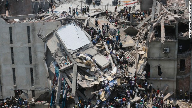 People rescue garment workers on Wednesday, April 24, after the building caved in, leaving a chaotic mass of broken concrete and twisted metal.