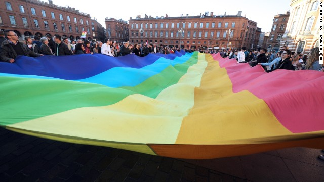 People unfurl a rainbow banner in Toulouse on April 23 after the lower house vote.