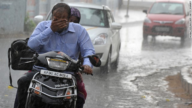 A commuter wipes his face while riding his scooter during heavy rain in Hyderabad, India, on Monday, April 22.